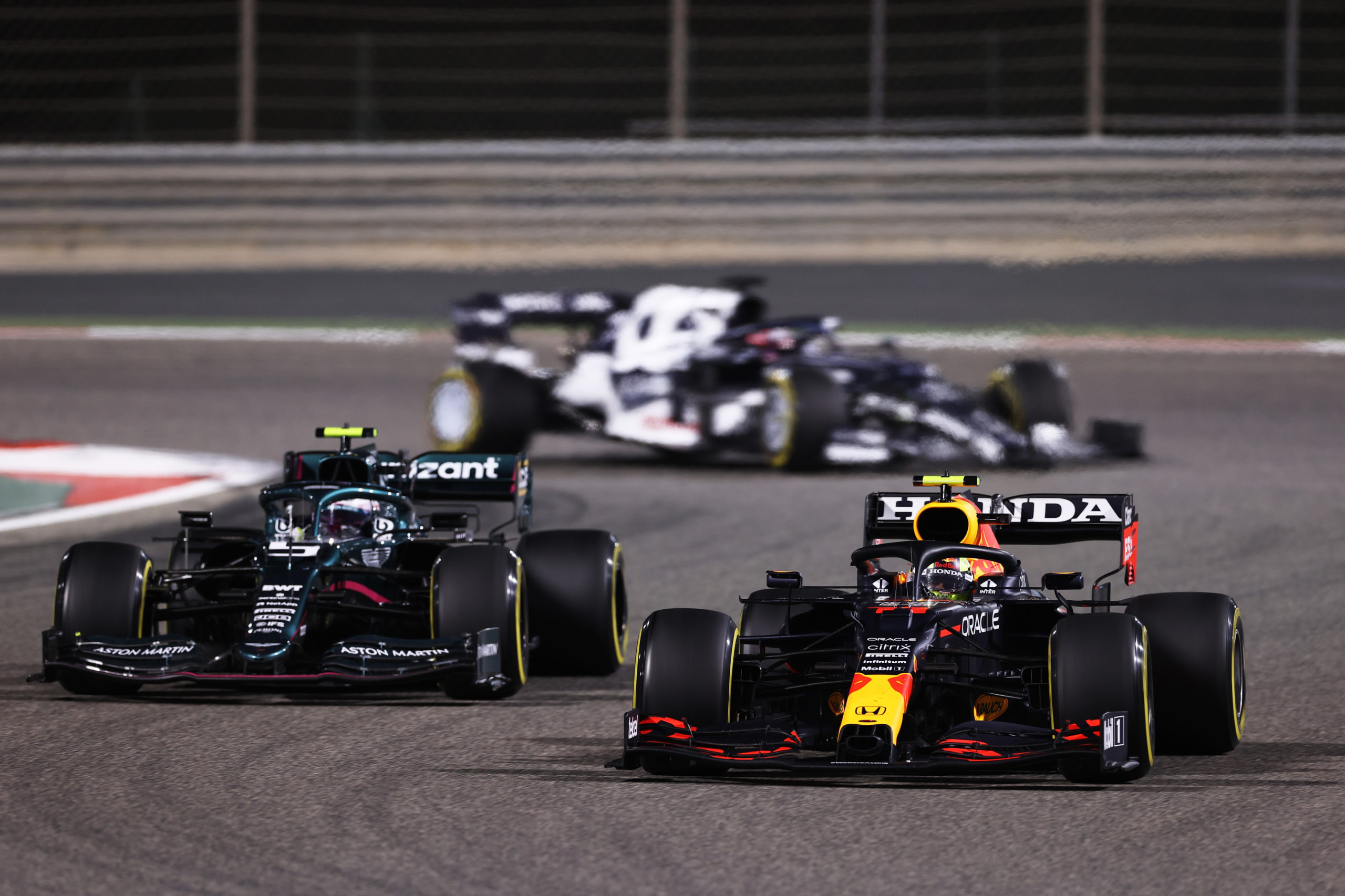 BAHRAIN, BAHRAIN - MARCH 28: Sergio Perez of Mexico driving the (11) Red Bull Racing RB16B Honda and Sebastian Vettel of Germany driving the (5) Aston Martin AMR21 Mercedes compete for position on track during the F1 Grand Prix of Bahrain at Bahrain International Circuit on March 28, 2021 in Bahrain, Bahrain. (Photo by Lars Baron/Getty Images) // Getty Images / Red Bull Content Pool  // SI202103280156 // Usage for editorial use only //